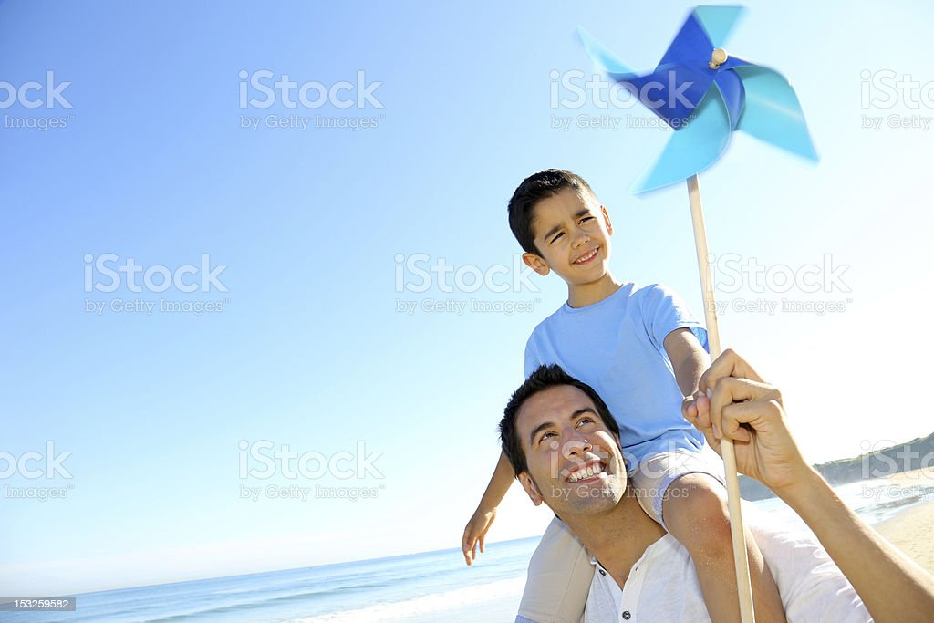 Father and son playing with paper windmill at the beach Little boy up on his fathers's shoulders holding swirl Adult Stock Photo