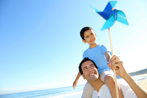 Father And Son Playing With Paper Windmill At The Beach Stock Photo - Download Image Now