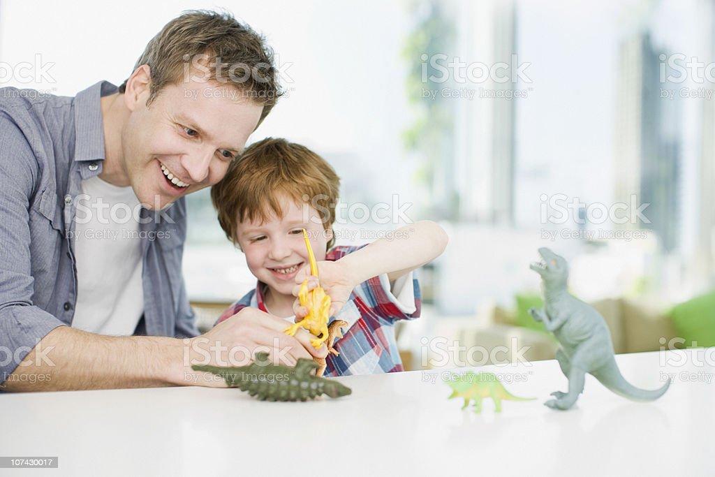 Pai e filho brincando com plástico dinossauros - foto de acervo