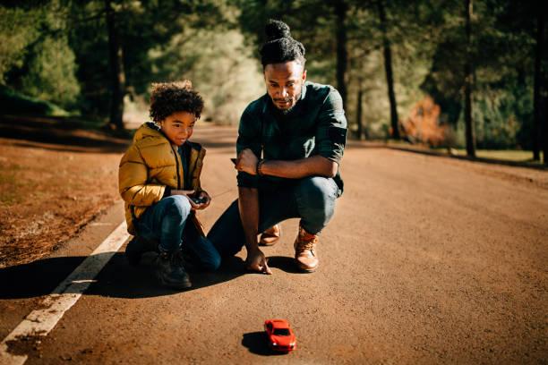 父と息子が遊んで自然のリモート制御車 - リモート ストックフォトと画像