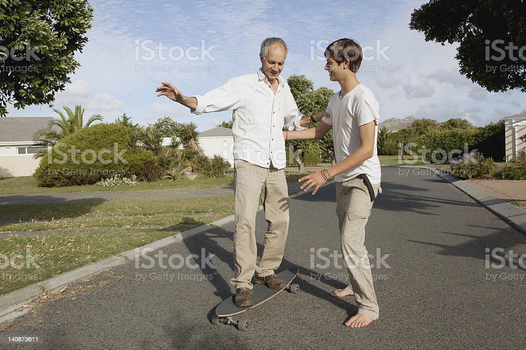 Padre e figlio giocano con skateboard - foto stock
