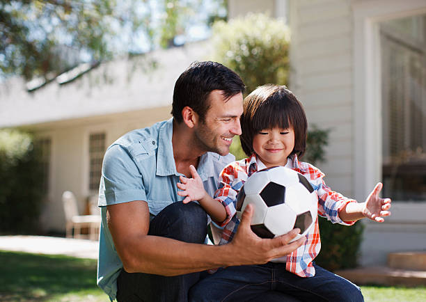 Father and son playing with soccer ball stock photo