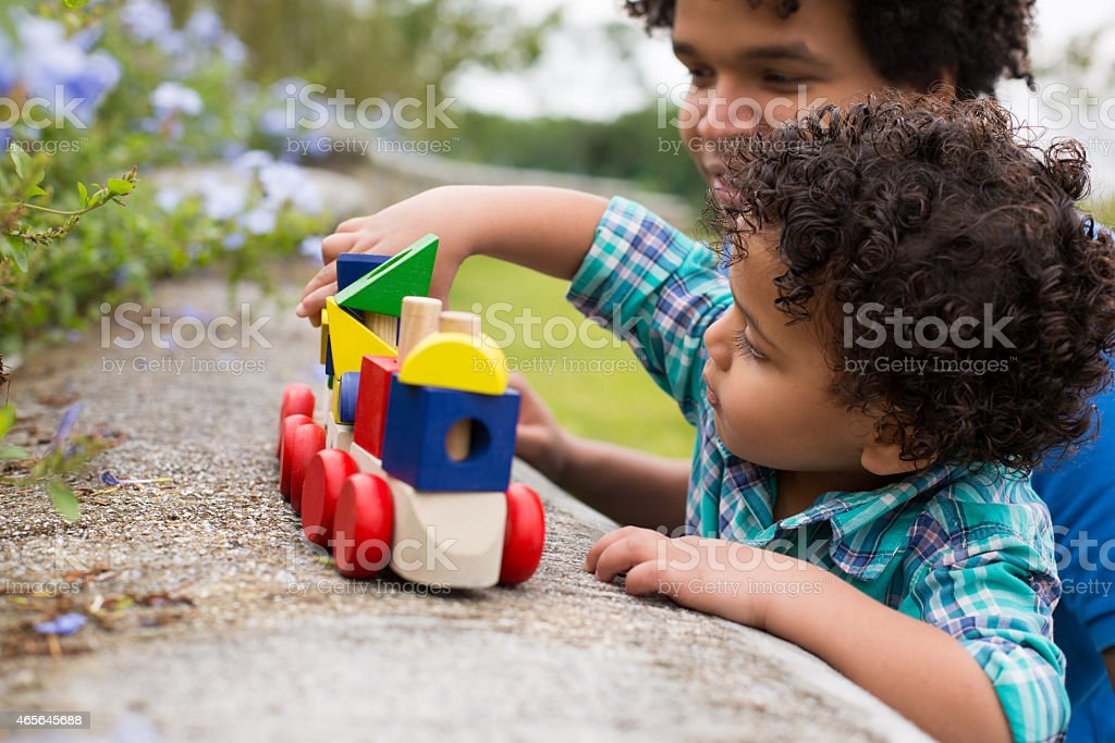 Father and son playing with toy train stock photo