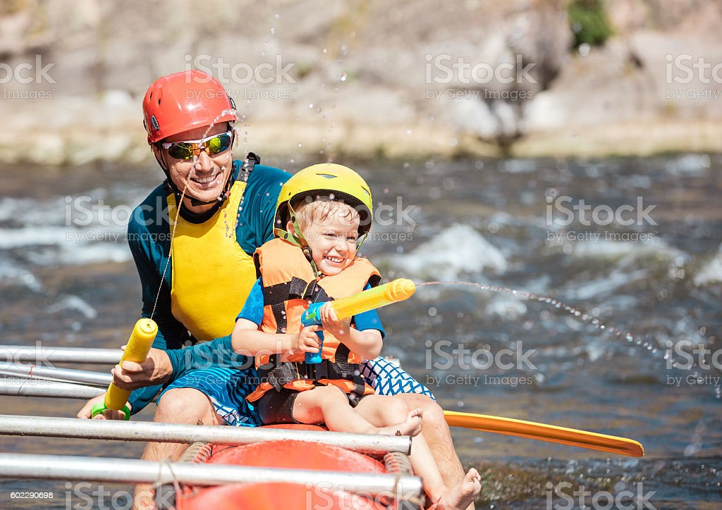 Father and son playing with water pistols stock photo