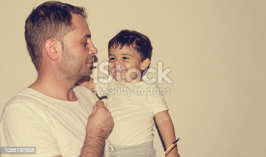 Father and son playng with moustache funny face expressions, family time