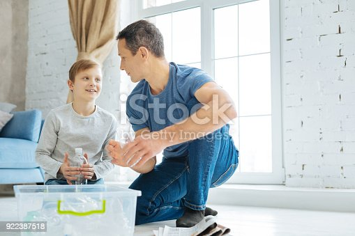 istock Father and son practicing in crushing bottles before recycling 922387518