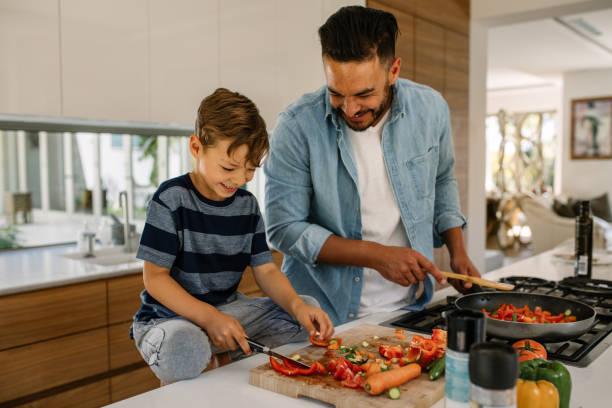 padre e figlio preparano cibo in cucina - cucinare foto e immagini stock