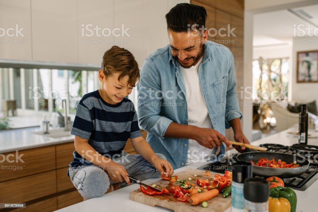 Father and son preparing food in kitchen stock photo