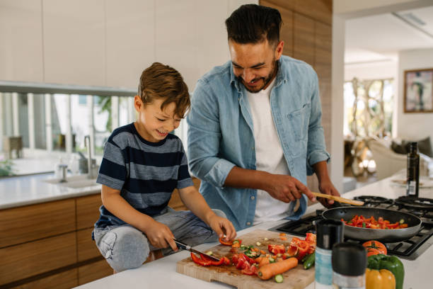 Father and son preparing food in kitchen Little boy cutting vegetables while his father cooking food in kitchen. Father and son preparing food at home kitchen. preparing food stock pictures, royalty-free photos & images