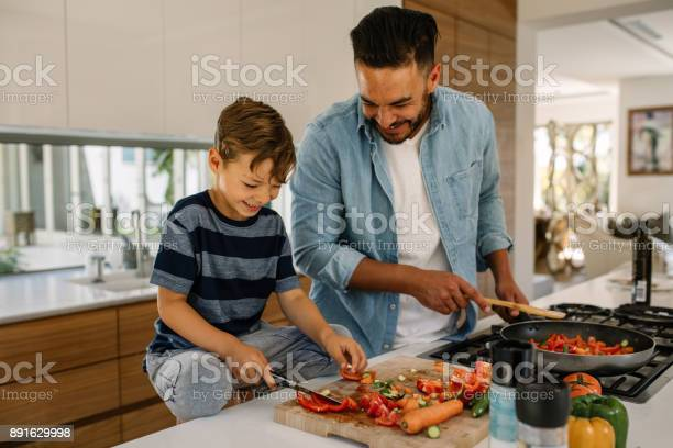 Little boy cutting vegetables while his father cooking food in kitchen. Father and son preparing food at home kitchen.
