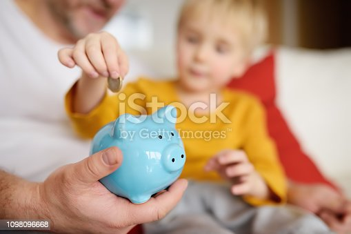 Father and son putting coin into piggy bank. Education of children in financial literacy