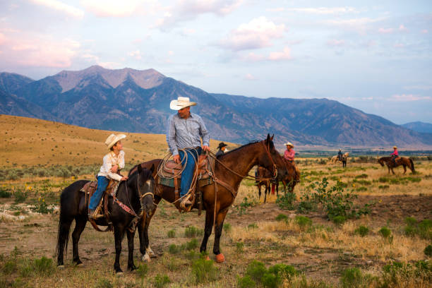 Father and Son Ranchers A father and son look over their ranch on horseback rancher stock pictures, royalty-free photos & images