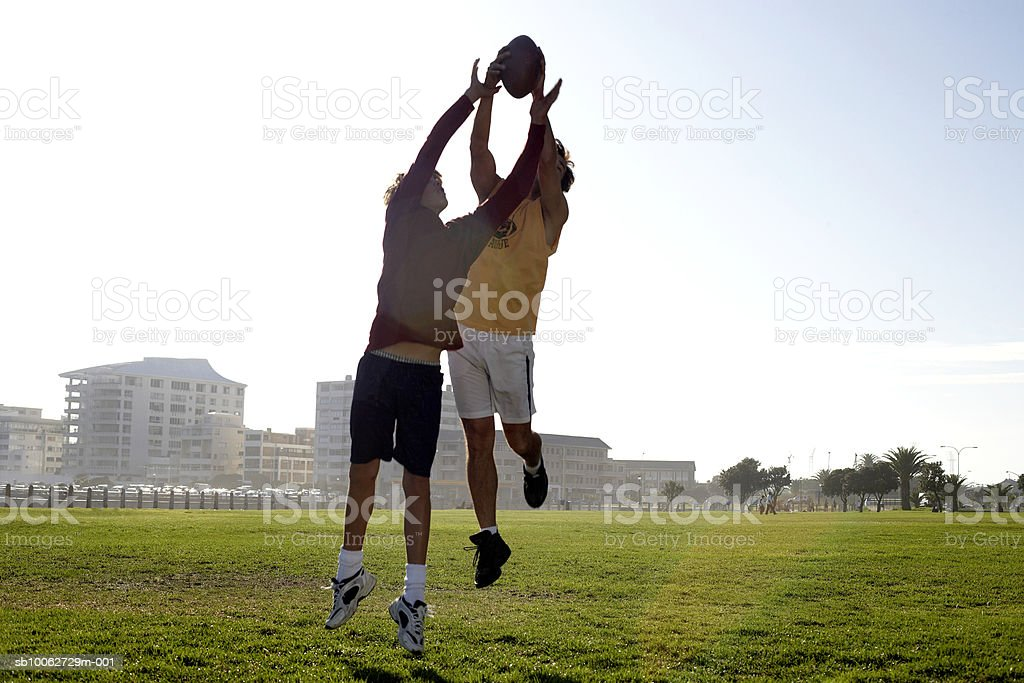 Father and son (14-15) reaching for football royalty free stockfoto