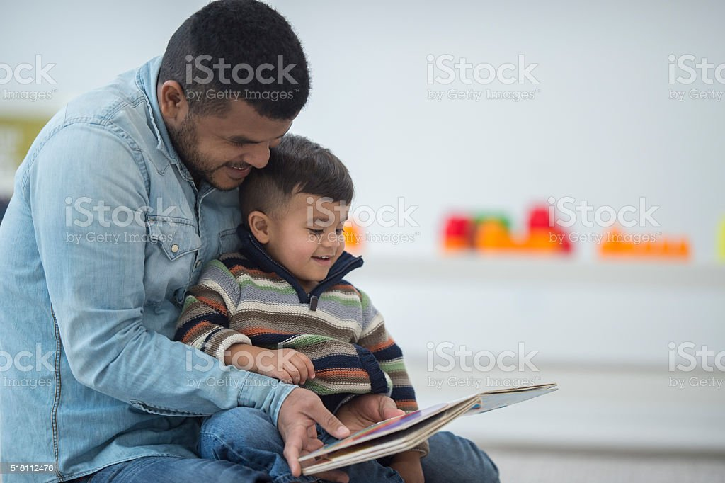 Father and Son Reading a Book Together stock photo