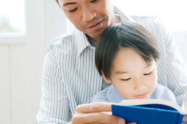 Father and son reading book stock photo