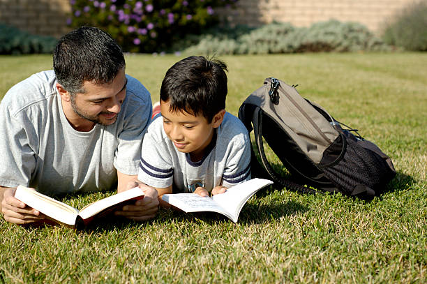 a father and son reading books on a grass lawn - young singles stock photos and pictures
