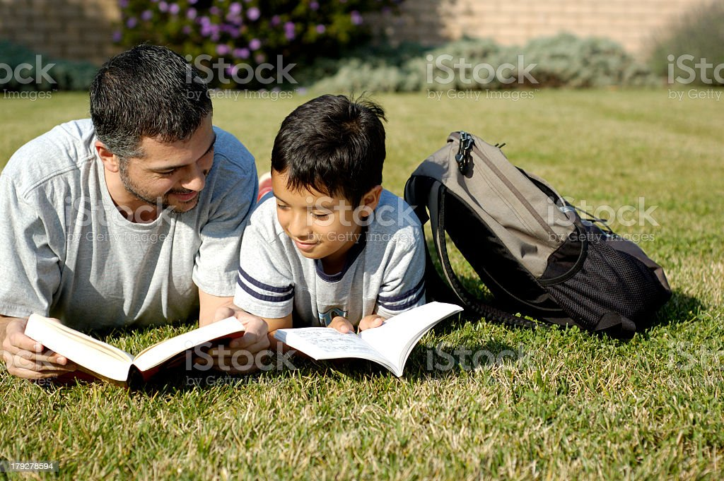 A father and son reading together stock photo