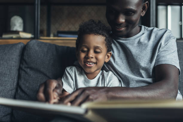 father and son reading together stock photo