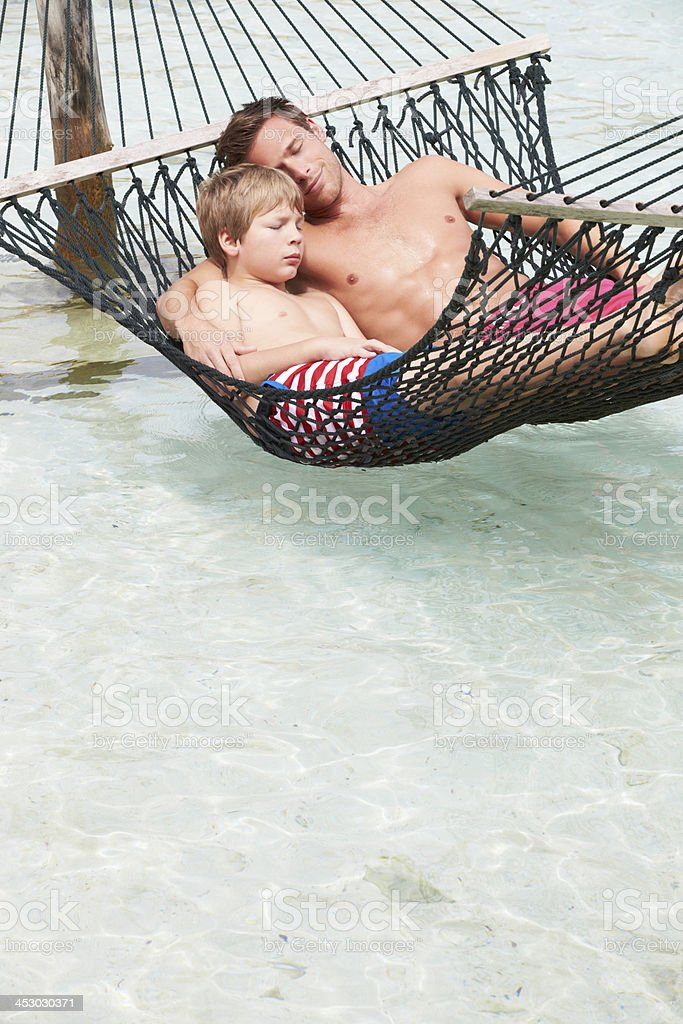 Father And Son Relaxing In Beach Hammock royalty-free stock photo