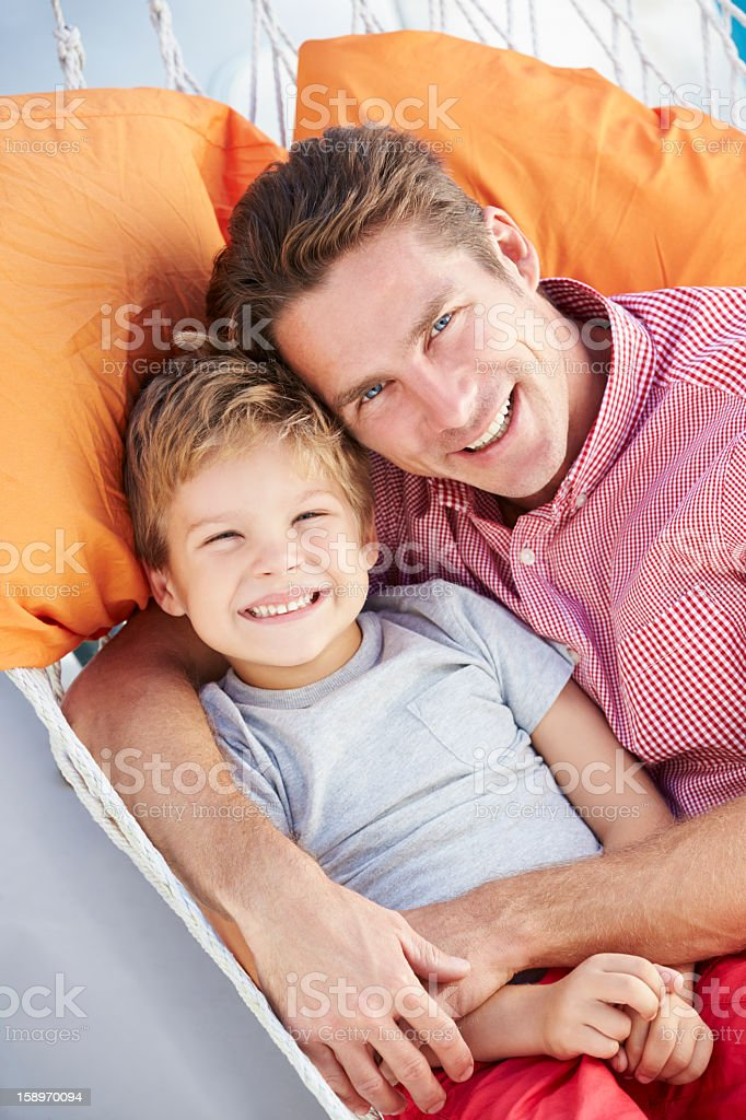 Father And Son Relaxing In Garden Hammock Together royalty-free stock photo