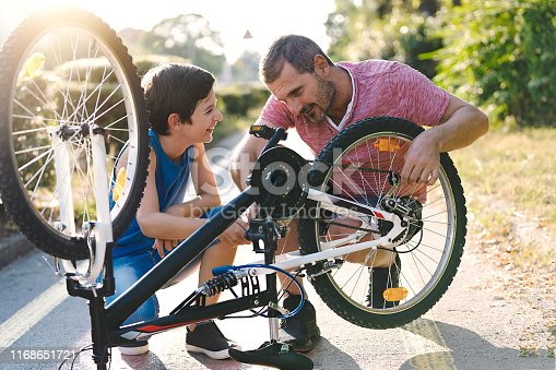 Father and son repairing a bicycle in city. Family cycling
