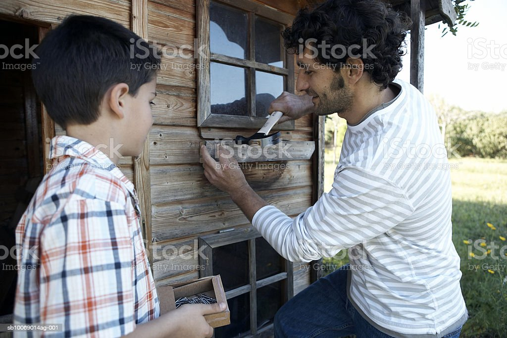 Father and son (8-9) repairing garden house 免版稅 stock photo