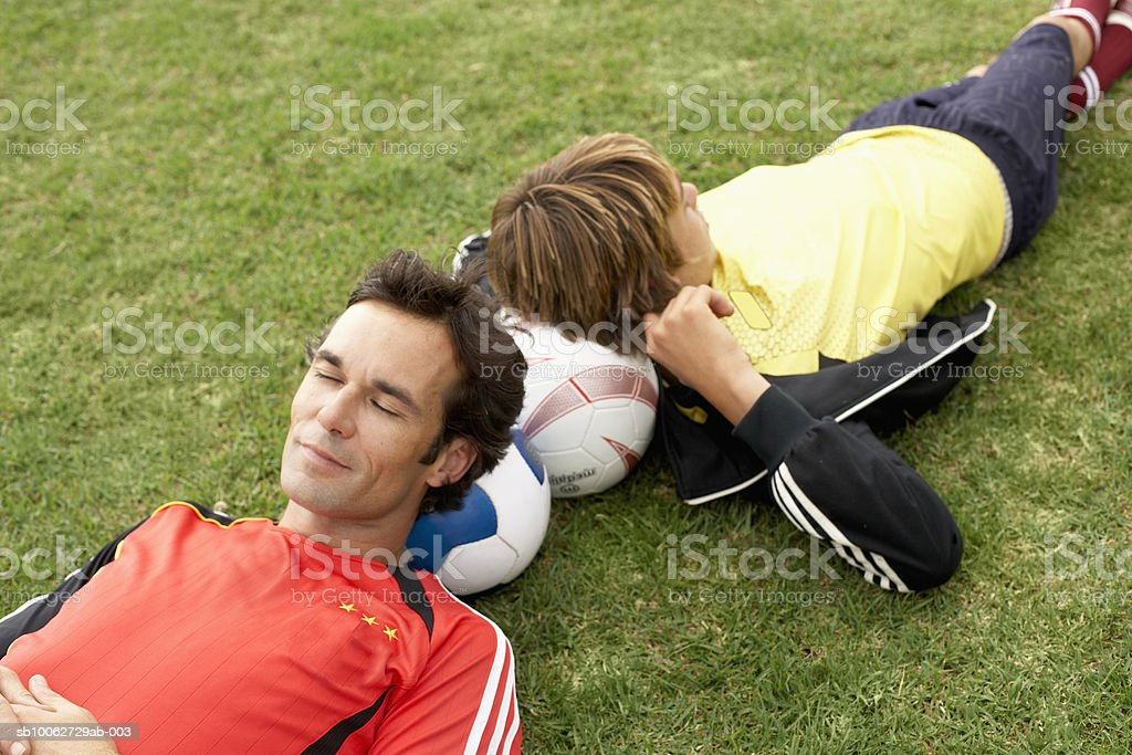 Father and son (14-15) resting head on football, elevated view Lizenzfreies stock-foto
