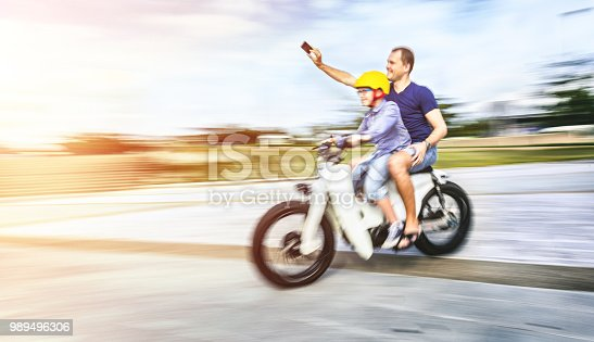 Father and son riding a bike and taking selfie
