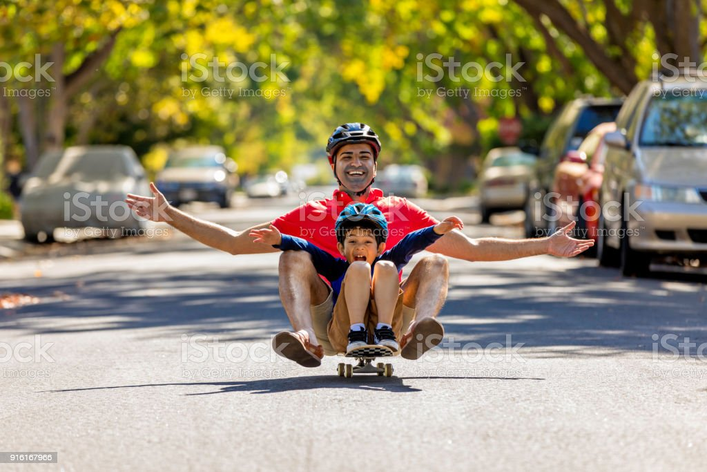 Father and Son Riding a Skateboard stock photo
