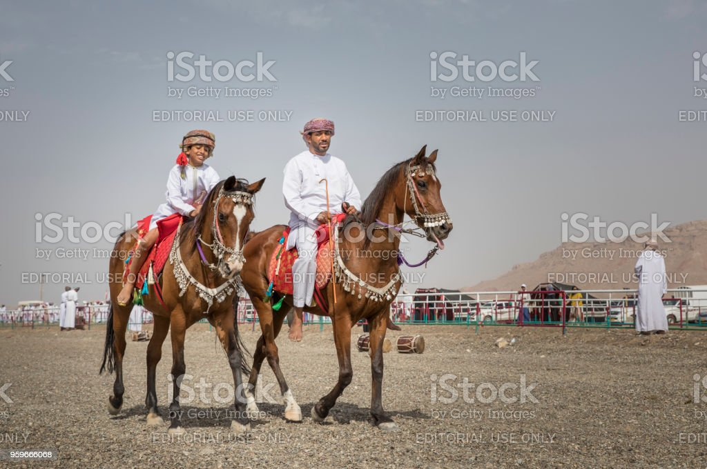father and son riding horses stock photo