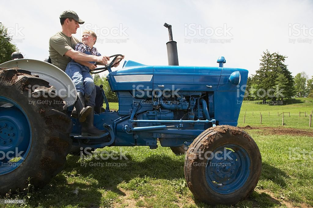 Father and son riding tractor on farm stock photo
