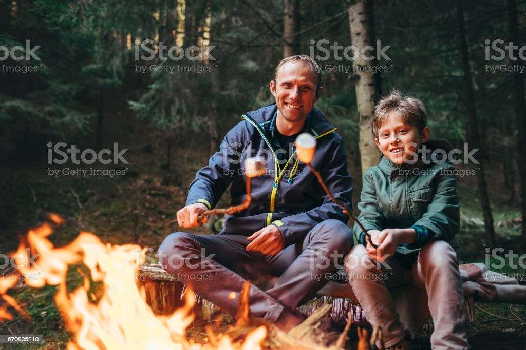 Father and son roast marshmallow candies on the campfire in forest stock photo