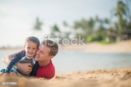 605742160 istock photo Father and Son Rolling in the Sand 501579990