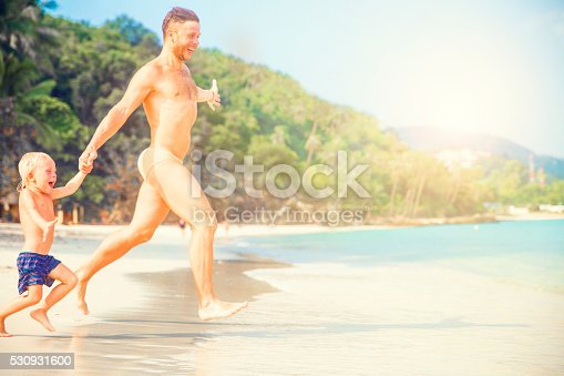 istock Father And Son Running Along Beach 530931600