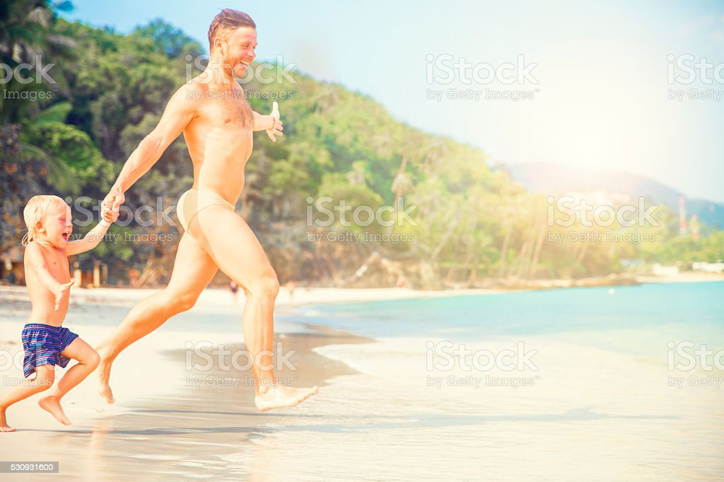 Father And Son Running Along Beach​​​ foto