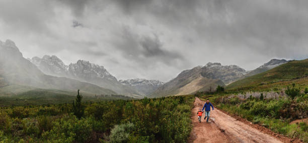 Father and Son Running Together between snow capped mountains stock photo