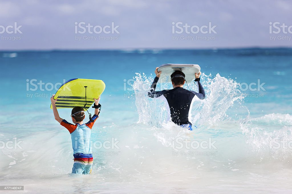 Father and son running with boogie boards stock photo