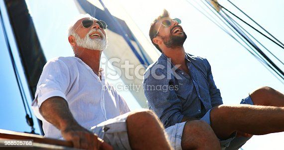 Closeup low angle view of mid 60's man and his son enjoying summer holiday on a sailboat. They are sitting on the deck, looking at the distance, talking and laughing.