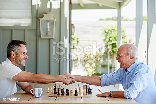 Side view of father and son shaking hands over chess set