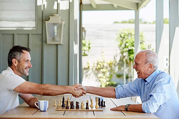 Father and son shaking hands over chess set stock photo