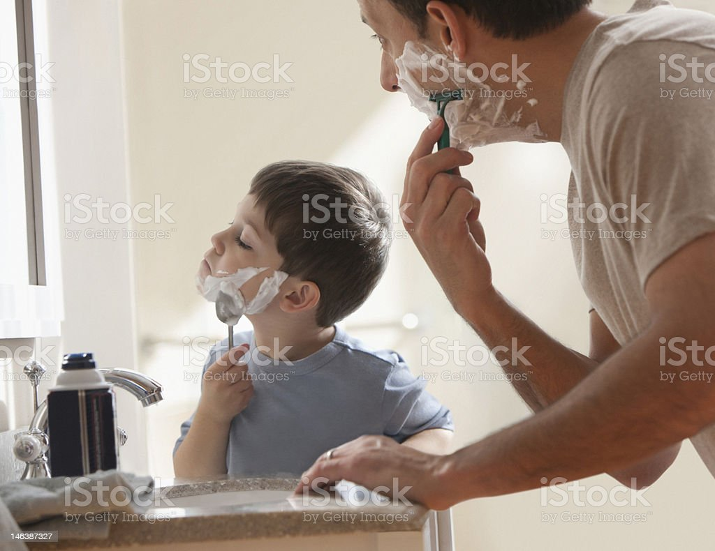 Father and son shaving together stock photo