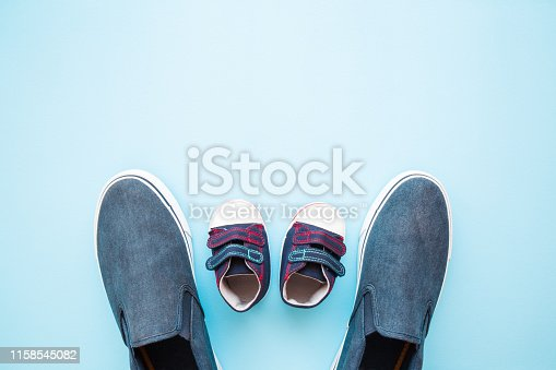 917262406istockphoto Father and son shoes on blue background. Love concept. Pastel color. Empty place for sentimental, inspiration text, positive quote or lovely, cute sayings. Flat lay. Top view. Closeup. 1158545082