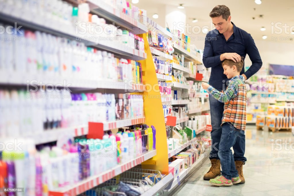 Father and son shopping for cosmetics stock photo