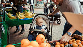 Dad and his young son in a pushchair out shopping. They have stopped to look at oranges.