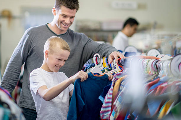 Father and Son Shopping Together A little boy and his father are looking through a rack of clothes while shopping together. The boy has pulled out a long sleeve shirt to buy. discount store stock pictures, royalty-free photos & images