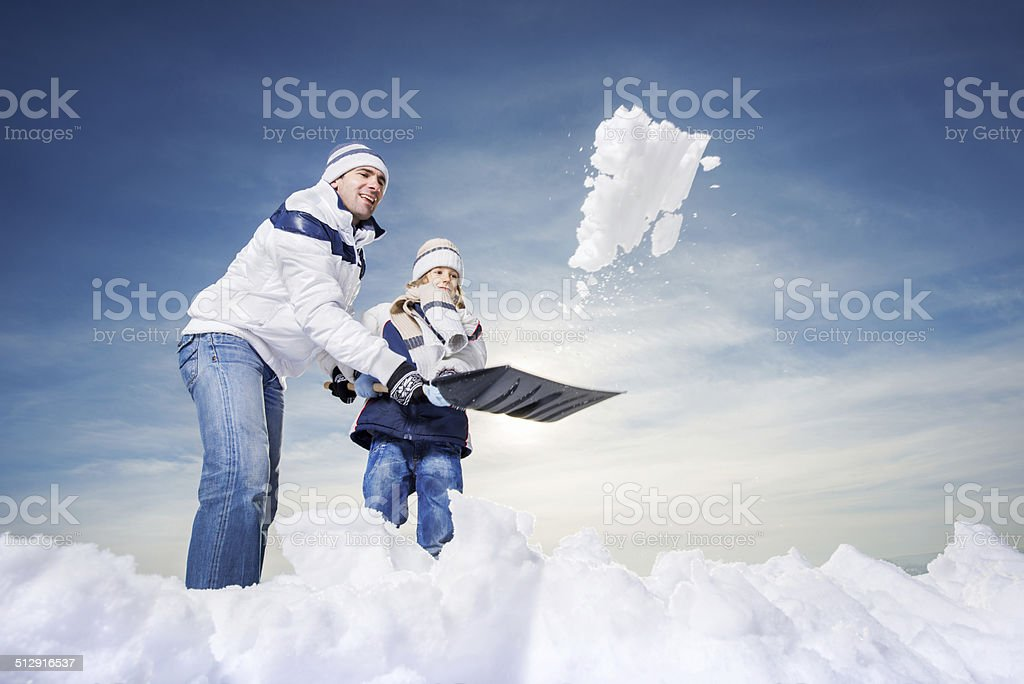 Father and son shoveling snow. stock photo
