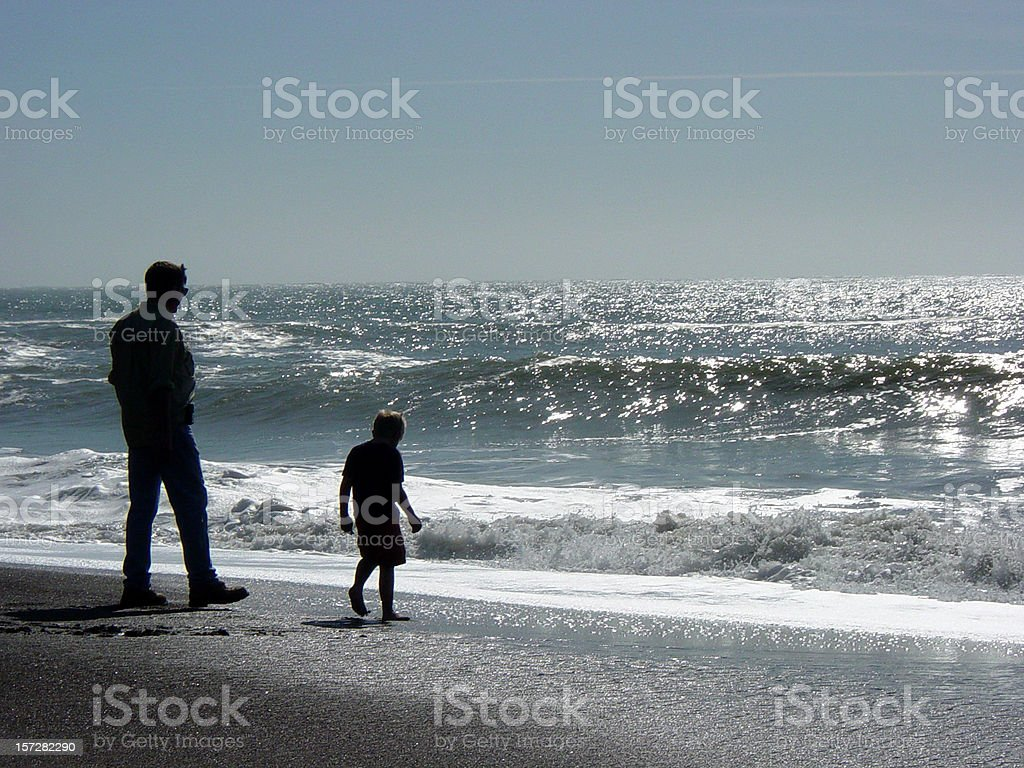 Father and Son Silhouettes by the Shore at the Beach royalty-free stock photo