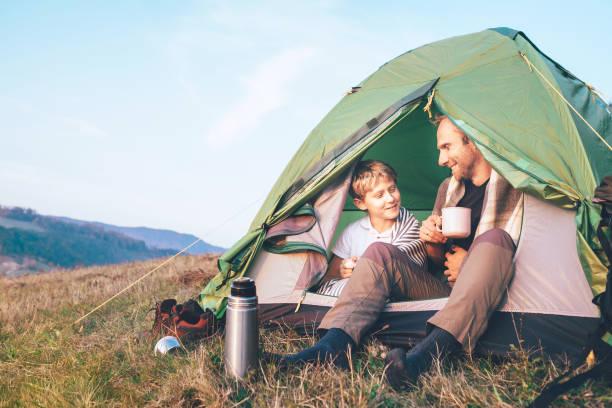 Padre e hijo se sentan en la tienda del campamento beber té caliente y tener conversación. Tiempo libre con el padre, la paternidad - foto de stock