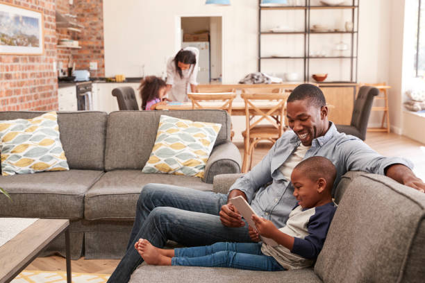 father and son sit on sofa in lounge using digital tablet - family room stock photos and pictures