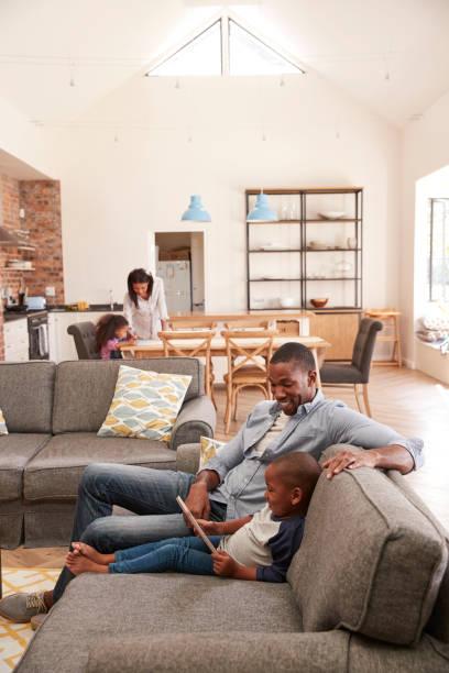 vater und sohn sitzen auf sofa in der lounge mit digitalem tablet - kinderküche zubehör stock-fotos und bilder